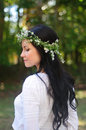 Portrait of a young woman with long black hair and flower crown side face in white shirt in garden Royalty Free Stock Photos
