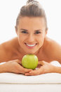 Portrait of young woman on massage table showing apple in spa salon Royalty Free Stock Photography