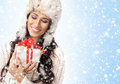 Portrait of a young woman opening a christmas present and attractive caucasian in winter hat holding the image is taken on light Stock Photos