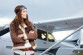 Portrait of young woman pilot in front of airplane. Royalty Free Stock Photo