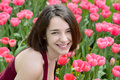 Portrait of a young woman in a pink tulip garden Royalty Free Stock Photo