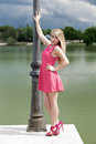 Portrait of young woman posing against the lamppost outdoor beautiful girl in front a lake with a cloudy sky Stock Photo
