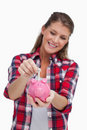Portrait of a young woman putting a note a piggy bank Royalty Free Stock Images