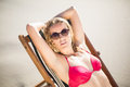 Portrait of young woman relaxing on an armchair on the beach a sunny day Royalty Free Stock Photo