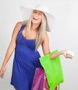 Portrait of a young woman smiling with her shopping bags laughing against white background Stock Photography