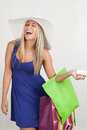 Portrait of a young woman smiling with her shopping bags laughing against white background Stock Photos