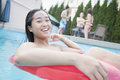 Portrait of young woman smiling and sitting on an inflatable tube in the pool Royalty Free Stock Photo