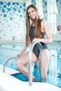 Portrait of a young woman in sport swimming pool with long hairs relaxing after fitness exercises indoor with blue water Royalty Free Stock Images