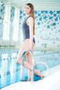 Portrait of a young woman in sport swimming pool with long hairs relaxing after fitness exercises indoor with blue water Stock Photo