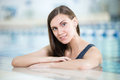 Portrait of a young woman in sport swimming pool with long hairs relaxing after fitness exercises indoor with blue water Stock Images