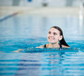 Portrait of a young woman in sport swimming pool with long hairs relaxing after fitness exercises indoor with blue water Royalty Free Stock Image