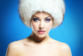 Portrait of a young woman in a white fur hat glamor and beautiful winter the image is taken on blue background Royalty Free Stock Photography