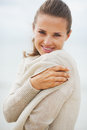 Portrait of young woman wrapping in sweater on coldly beach with long hair Stock Photos