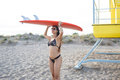 Portrait of a young women dressed in trendy swimwear going to the beach with her surfboard, surfer female in bikini with perfect