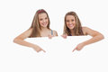 Portrait of young women holding and pointing a blank sign Stock Photography