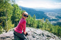 Portrat of happy little girl sitting on rocky cliff in the moun