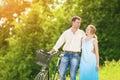 Portret kaukaska para ma przespacerowanie w parku z rowerem Zdjęcia Royalty Free
