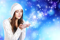 Portriat of a young woman in a hoodie holding snow and beautiful winter clothes the image is taken on blue and sparkly background Royalty Free Stock Photo