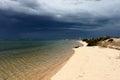 Portugal. Algarve. Ilha deserta. Sand and ocean before storm on dark blue sky background, horizontal view. Royalty Free Stock Photo