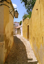 Portuguese village street a typical old narrow in portugal bathed in sunshine with a lamp and calçada cobbled paving Stock Photography