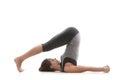 Pose halasana sporty yoga girl on white background in plow Royalty Free Stock Photography
