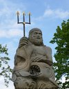 Poseidon statue with trident and fish against blue sky Stock Images