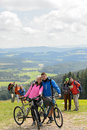Posing cyclist couple on the mountain top with bikes Royalty Free Stock Photos