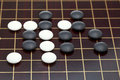 Position of stones during go game playing on wooden goban Royalty Free Stock Photography