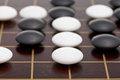 Position of stones during go game playing on wooden goban close up Royalty Free Stock Photography