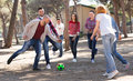 Positive adults chasing ball outdoors Royalty Free Stock Photo