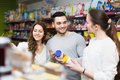 Positive adults choosing tinned food people at supermarket Royalty Free Stock Photos