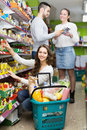 Positive adults choosing tinned food young at supermarket Stock Images