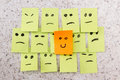Positive attitude concept for a with small office notes with multiple faces and one that stands out with a smile Stock Image