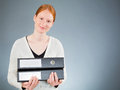 Positive businesswoman with folders a smiling or an assistant holding two black in her hands and looking at the camera Royalty Free Stock Images