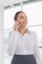 Positive businesswoman standing while talking on phone in her office Stock Photos