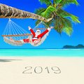 Positive Christmas Santa Claus relax in hammock at palm beach and Happy New Year 2019 caption at white sand Royalty Free Stock Photo