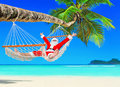 Positive Christmas Santa Claus relax in hammock at palm beach Royalty Free Stock Photo