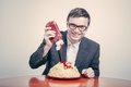 Positive consumerism concept happy businessman pouring ketchup on large dish of pasta Royalty Free Stock Photos