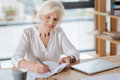 Positive elderly woman taking notes Royalty Free Stock Photo