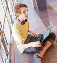 Positive expression teen boy with laptop and headphone Royalty Free Stock Photo