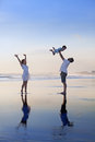 Positive family having fun on black sand sea beach Royalty Free Stock Photo