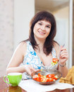 Positive girl eats veggie salad on sofa at home interior Royalty Free Stock Image