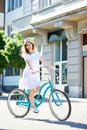 Positive girl smiling to the camera while riding blue bike in city center with beautiful buildings and green trees Royalty Free Stock Photo