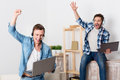 Positive guys expressing gladness we are the winners cheerful overjoyed handsome jubilant holding laptop and playing games while Royalty Free Stock Photography
