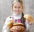 Positive joyful little girl with bread cheerful is holding a lot of loaves of Royalty Free Stock Images