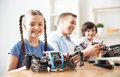 Positive kids playing with lego happy childhood delighted nice girl smiling and sitting at the table while her father and brother Stock Photos