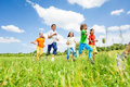 Positive kids playing and running in the field Royalty Free Stock Photo