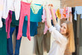Positive long haired girl drying clothes on clothes line after laundry Stock Photos