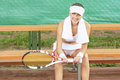 Positive looking professional female tennis player having rest o on bench of court and smiling horizontal image Royalty Free Stock Photos