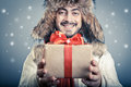 Positive male with magical giftbox giving a red ribbon and smiling Royalty Free Stock Images